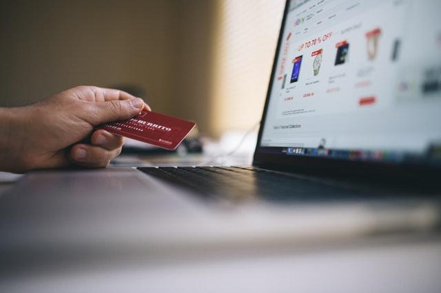 Man med betalkort framför datorn